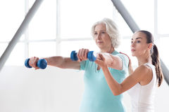 Determined persistent woman holding dumbbells in front of her. Develop your body. Serious confident persistent women standing near the coach and looking forward Royalty Free Stock Photos