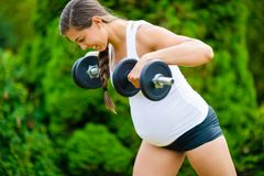 Determined Pregnant Woman Doing Back Workout With Dumbbells In P royalty free stock images