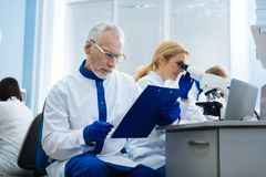 Determined researchers analysis genes in the lab. Making gene analysis. Serious skilful professional researchers working in the lab and conducting a research Stock Photo