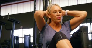 Senior woman doing abs workout in fitness studio 4k