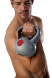 Determined shirtless sportsman exercising with kettle bell