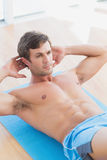 Determined shirtless young man doing sit ups Royalty Free Stock Images