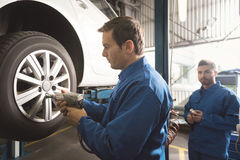 Determined skilled worker fixing the wheel Royalty Free Stock Photo