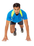Determined Sportsman At Starting Line. Full length portrait of determined sportsman at starting line against white background. Vertical shot Royalty Free Stock Photos