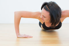Determined sporty woman doing push ups in fitness studio Stock Photos