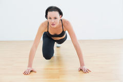 Determined sporty woman doing push ups in fitness studio Stock Image