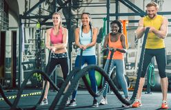 Determined and strong cheerful people during functional training. Determined and strong cheerful people exercising together with heavy battle ropes during stock image