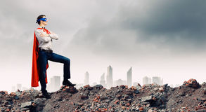 Determined superman. Confident superman in cape and mask standing on ruins royalty free stock photo