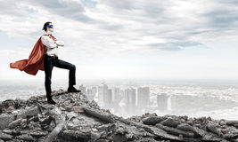 Determined superman. Confident superman in cape and mask standing on ruins Stock Photography