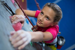 Determined teenage girl practicing rock climbing. In fitness studio stock images