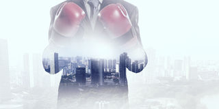 Determined to fight for success . Mixed media. Businessman in boxing gloves against cityscape background ready to fight stock images