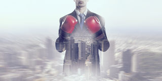 Determined to fight for success . Mixed media. Businessman in boxing gloves against cityscape background ready to fight royalty free stock photography