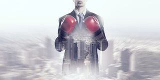 Determined to fight for success . Mixed media. Businessman in boxing gloves against cityscape background ready to fight stock photo
