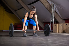 Determined to lift some weights. Pretty Latin girl about to lift a barbell during her workout at a cross-training gym Royalty Free Stock Image