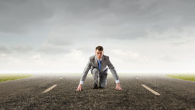 He is determined to start now. Young businessman on road ready to run race Royalty Free Stock Images