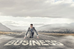He is determined to start now. Young businessman on road ready to run race Royalty Free Stock Photography