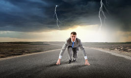 He is determined to start now. Young businessman on road ready to run race Stock Images