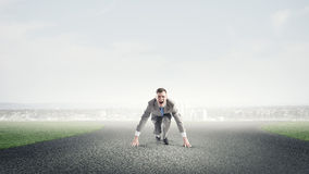 He is determined to start now. Young businessman on road ready to run race Royalty Free Stock Image