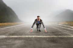He is determined to start now. Young businessman on road ready to run race Royalty Free Stock Photos