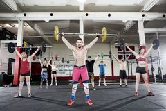Trainer With Clients Lifting Barbells In Fitness Club. Determined trainer with male and female clients lifting barbells in fitness club stock image