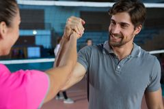 Determined volleyball player holding hand with teammate Royalty Free Stock Images