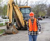 Determined walk. Road construction worker, walks determinately toward the camera. Bulldozer and residential area on the background Royalty Free Stock Photography