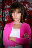 Determined wind blown girl. A closeup of a determined wind blown dark haired little girl wearing a pink sweater with arms crossed. Red leaves in background Stock Images