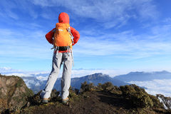 Determined woman backpacker hiking on mountain peak Stock Image
