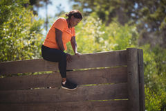 Determined woman climbing wooden wall during obstacle course Royalty Free Stock Images