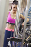 Determined woman doing exercises in gym on lat machine Stock Photos