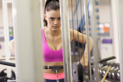 Determined woman doing exercises in gym on lat machine Royalty Free Stock Photo