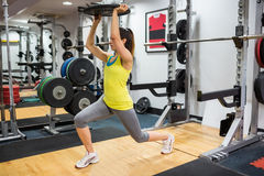Determined woman doing lunges while holding a weight overhead Royalty Free Stock Images