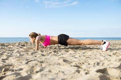 Determined Woman Doing Push-Ups On Beach Royalty Free Stock Photos