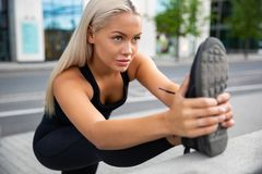 Determined Woman Doing Stretching Exercise At Sidewalk Railing royalty free stock photography