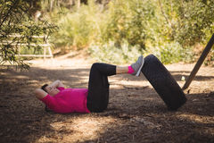 Determined woman exercising with huge tyre during obstacle course royalty free stock photos