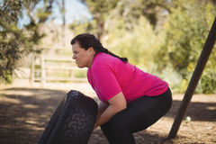 Determined woman exercising with huge tyre during obstacle course Stock Photos