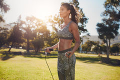 Determined woman exercising with jump rope in nature Royalty Free Stock Image