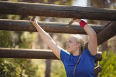 Determined woman exercising on monkey bar during obstacle course. In boot camp Royalty Free Stock Photos