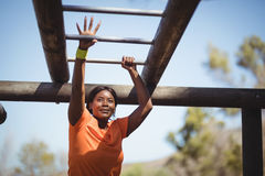 Determined woman exercising on monkey bar during obstacle course. In boot camp Stock Photo