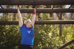 Determined woman exercising on monkey bar during obstacle course. In boot camp Stock Image