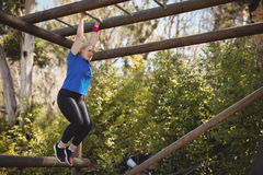 Determined woman exercising on monkey bar during obstacle course royalty free stock image