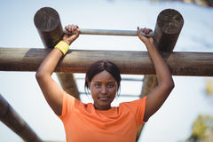 Determined woman exercising on monkey bar during obstacle course. In boot camp Stock Images