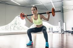 Determined woman holding a barbell behind the neck during functi Stock Image