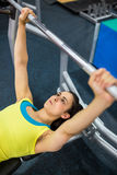 Determined woman lifting a barbell Stock Image