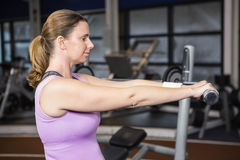 Determined woman lifting dumbbells Stock Image