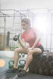 Determined woman lifting kettlebell in crossfit gym Stock Image