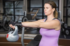 Determined woman lifting kettlebell Stock Photography