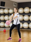 Determined Woman Lifting Kettlebell In Health Club Stock Photography