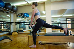 Determined woman performing stretching exercise on reformer Stock Photography