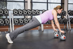 Determined woman planking with kettlebells Royalty Free Stock Photo